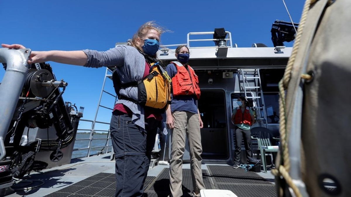 Researchers Melinda Baerwald (left) and Andrea Schreier (center) stand at the stern of a research vessel on the San Joaquin River off Antioch, California. (Photo: Reuters)