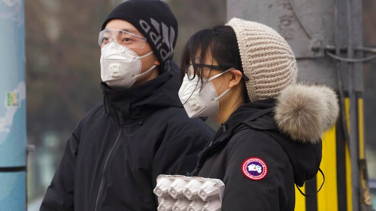 Residents wearing masks wait at a traffic light in Beijing, China Thursday, Feb. 13, 2020. (Photo: AP)