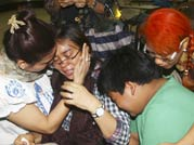 Relatives weep as they wait for the news on survivors