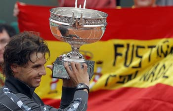 The Spanish flag is seen in the background as Rafael Nadal of Spain holds the trophy