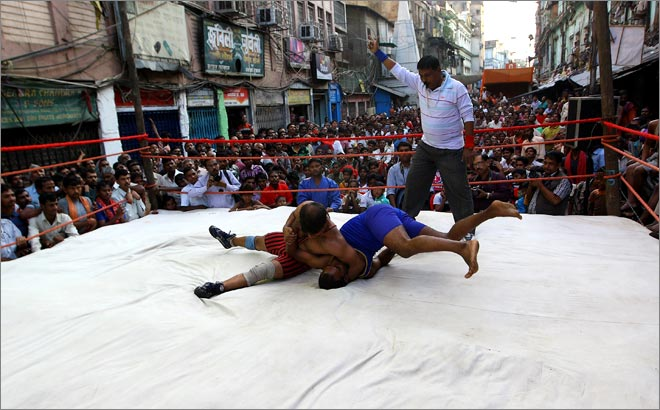 Wrestlers slug it out in a make-shift ring as spectators enjoy the match in Kolkata.
