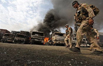 Afghan policemen investigate the site of the suicide attack in Afghanistan.