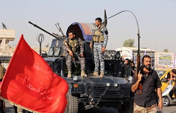 Iraqi federal policemen watch Shiite tribal fighters deploy with their weapons