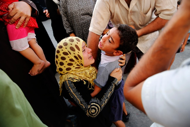 A Palestinian woman whose husband was killed by Israeli shelling during an Israeli ground offensive, embraces her son after finding him alive at the hospital in Beit Lahita in the northern Gaza Strip on July 30.