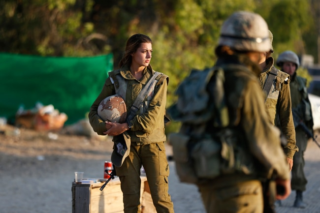 An Israeli soldier looks on at a staging area outside the northern Gaza Strip.