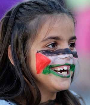 A girl with the Palestinian flag painted on her face smiles as people protest against Israel's military action in Gaza during a demonstration in Valencia.