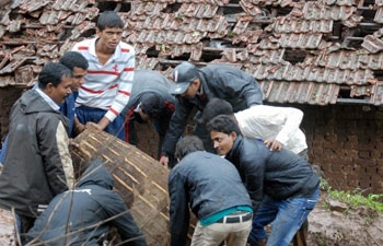 Rescue workers clear the debris at the site of a landslide in Malin village near Pune on July 30.