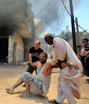 Palestinians evacuate a wounded man following what police said was an Israeli air strike on a house in Rafah in the southern Gaza Strip on July 20.