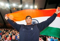 Vikas Shive Gowda celebrates with the Indian flag after winning the gold medal in the men's discus final.