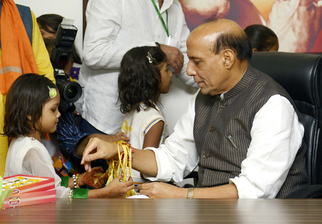 A young girl ties a rakhi on Minister of Home Affairs Rajnath Singh's wrist.