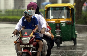 A man rides bike in rains with family on the day of rakshabandhan.