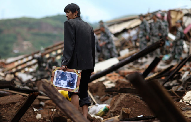 A man holds a picture in earthquake hit Longtoushan township of Ludian county, Yunnan province.