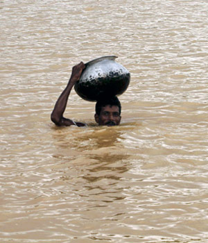 A villager on his way to collect drinking water wades through flood waters carrying a vessel on his head in Patapur village in Jajpur distict of Odisha.