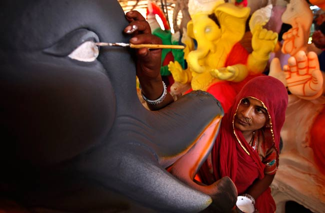 An Indian artisan adds finishing touches to an idol of elephant-headed Hindu god Ganesha at a workshop on the outskirts of Chennai, on Monday, Aug. 19, 2014.