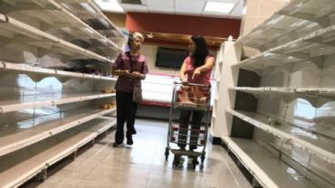 People walk past empty shelves at a supermarket in Caracas.