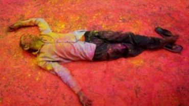 A Hindu devotee, smeared in coloured powder, takes a rest on a road during a procession for Holi celebrations in Kolkata