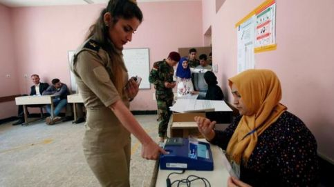 A member of Kurdish peshmerga casts her vote at a polling station two days before polls open to the public in a parliamentary election in Erbil, Iraq.