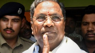 Mysore: Karnataka Chief Minister Siddaramaiah shows his ink stained finger after voting in the Karnataka Assembly elections 2018, at Hundi village in Mysore on Saturday. PTI Photo