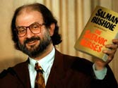 Author Salman Rushdie with a copy of his banned book The Satanic Verses.