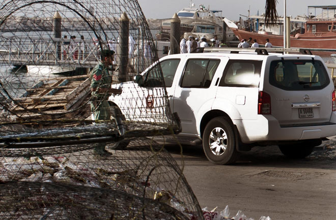 Emirati officials inspect a boat docked in a fishing harbor