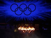 Olympic flame burns as the Olympic rings stand illuminated