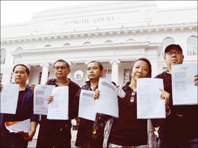 Filipino journalists and some media group leaders hold their petitions against the Cybercrime Prevention Act .