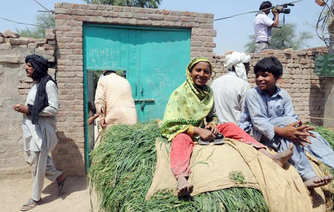 Villagers pass by the house of Kasab in Faridkot