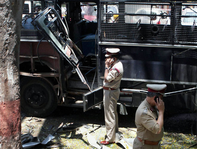 Police personnel inspect the site of the Bangalore blast