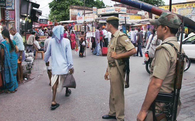 Policemen keep a vigil in a market area. There is heavy deployment of police and paramilitary forces in Ayodhya.