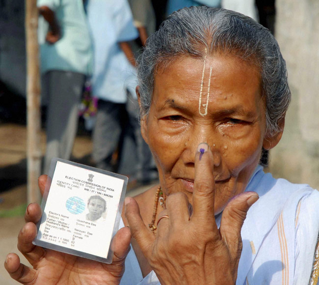 An old woman showing her inked finger after casting vote
