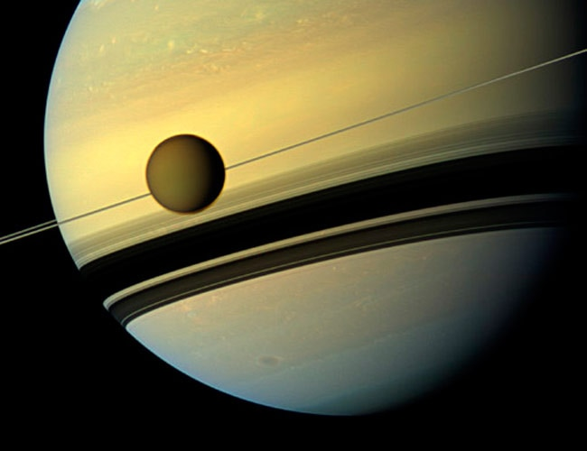 Titan, Saturn's largest moon appears before the planet.