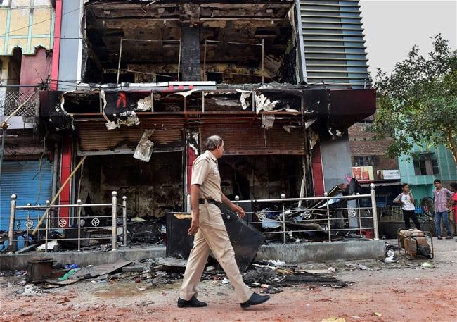 A policeman walks past a burnt shop in Trilokpuri on Sunday. Photo: PTI