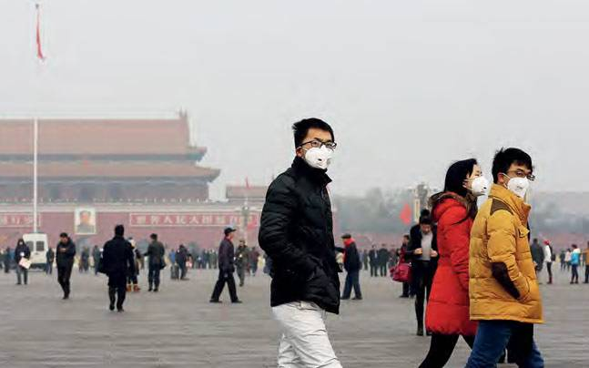 Tourists in face masks brave heavy smog at Tiananmen Square in Beijing