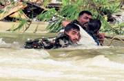 Army personnel rescue a man from a flooded locality
