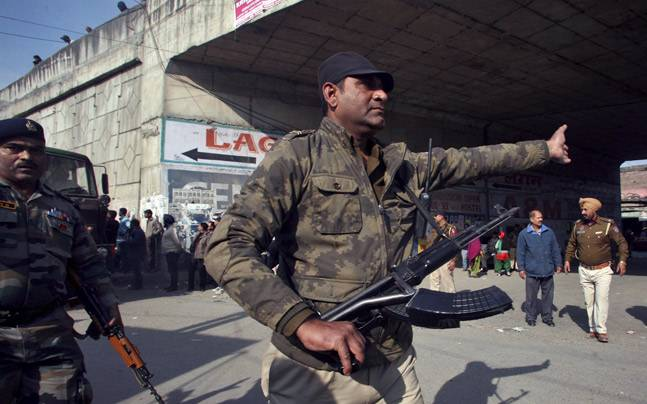 A security personnel asks people to move away from the area outside the Indian Air Force base at Pathankot. (Photo: Reuters)
