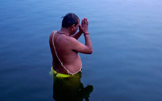 A Hindu devotee stands in the waters of River Ganga to offer prayers to the Sun God at dawn in Varanasi. Picture courtesy: Reuters