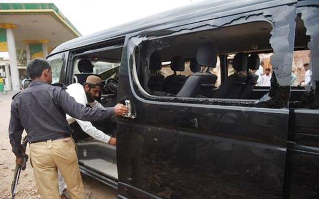 Pakistani security officials examine a vehicle attacked in Karachi
