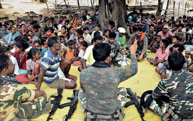 The police interact with villagers at a 'gram bhent' in Gaderi village.
