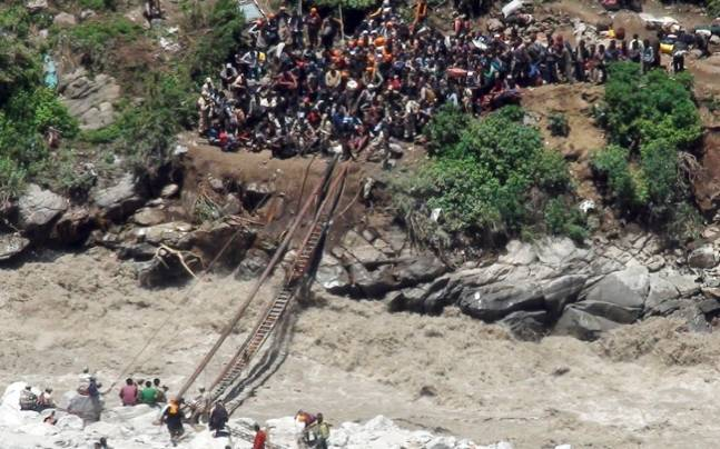 Indo-Tibetan Border Police personnel, in uniform, help stranded pilgrims on a makeshift bridge cross a stream of gushing floodwater on June 21, 2013 (Image: AP)