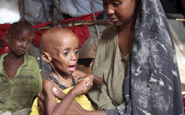An internally displaced Somali woman holds her malnourished child inside their temporary home in Hodan district, south of Somalia's capital Mogadishu, September 20, 2011: Reuters