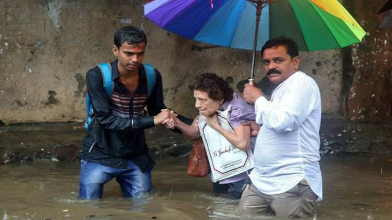 A woman is helped to move through a water-logged road after rains in Mumbai (Photo: Reuters)