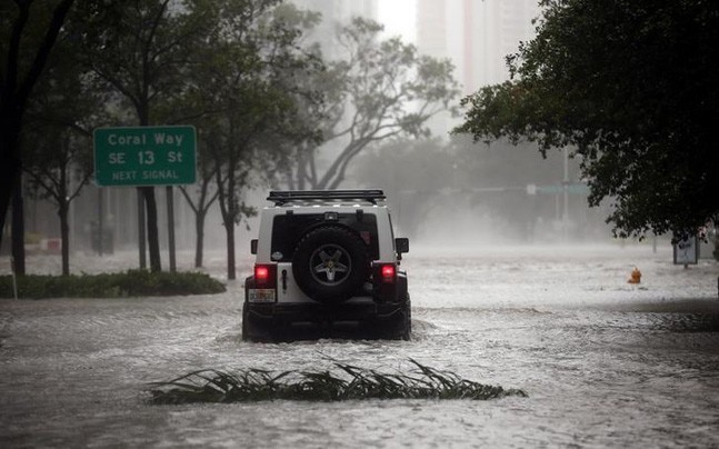 A vehicle drives along a flooded street in downtown Miami as Hurricane Irma arrives at south Florida, US