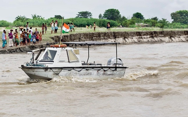 Bangladeshi villagers watch as coast guard boats patrol the Brahmaputra on the border in Assam. (Photo: Anupam Nath / AP)