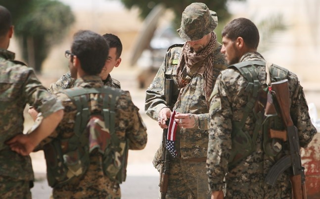 US fighter stands with SDF fighters in Raqqa