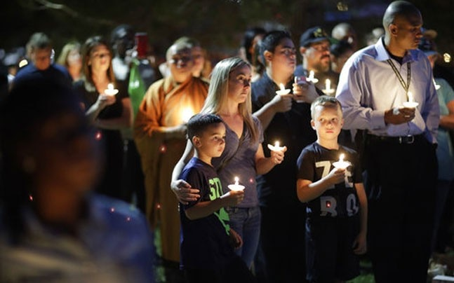 People attend a candlelight memorial for Las Vegas police officer Charleston Hartfield, who was killed when Stephen Craig Paddock broke windows on the Mandalay Bay resort and casino and began firing with a cache of weapons at a country music festival. (Ph