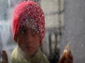 A Palestinian girl looks through a plastic sheet as raindrops are seen, outside her family's house in Al-Shati refugee camp in Gaza City January 17, 2018.
