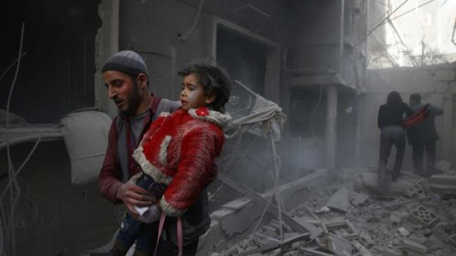 Man carries child among rubble in Eastern Ghouta. Photo: Reuters/Bassam Khabieh