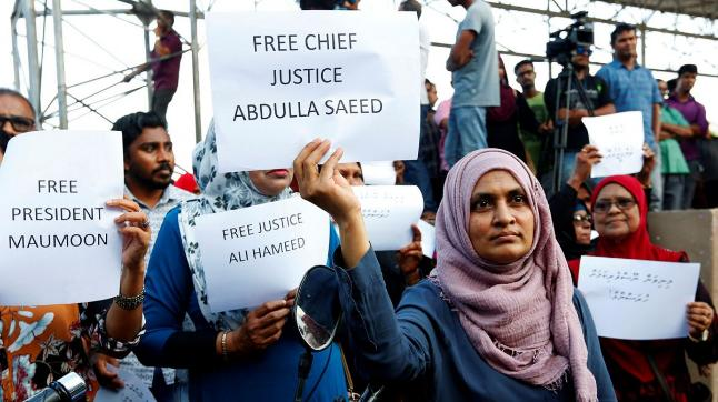 Maldivian opposition supporters holds placards near the main opposition Maldives Democratic Party (MDP) headquarters during a protest.