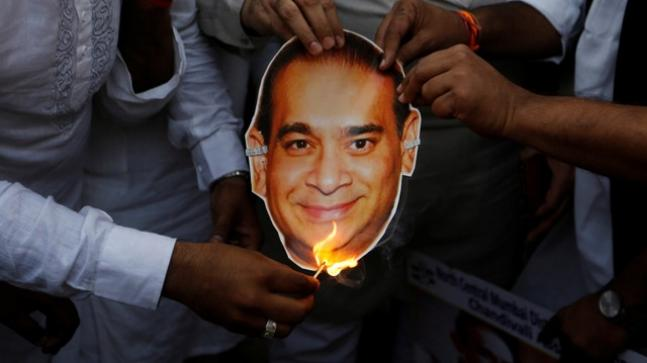 Political activists burn a picture of Nirav Modi