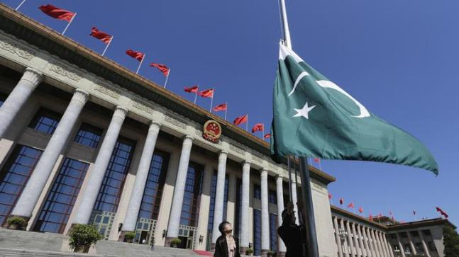 A staff member raises Pakistan's flag in front of the Great Hall of the People in Beijing.